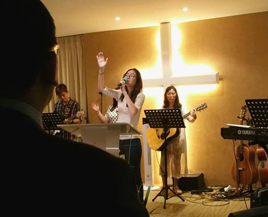 You Qian leading worship during service